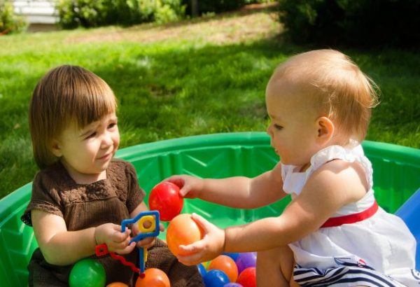 Photo: Two baby girls in a pool filled with balls.